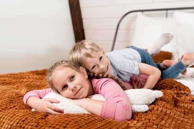 Bambini della foto a figura intera che si situano a letto