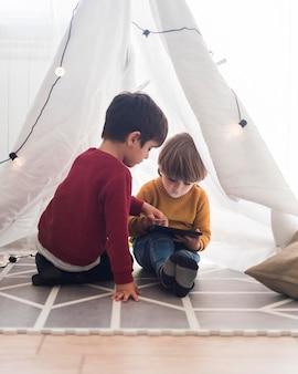 Bambini della foto a figura intera in tenda fatta in casa