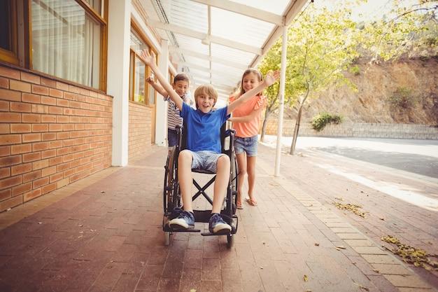 Bambini della scuola che spingono un ragazzo sulla sedia a rotelle