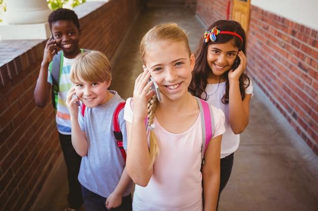 Bambini della scuola che utilizzano i cellulari nel corridoio della scuola