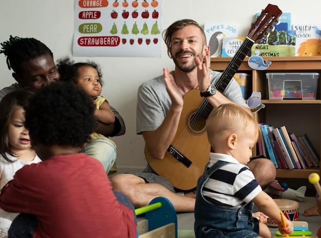 Bambini della scuola materna che giocano con gli strumenti musicali nell'aula