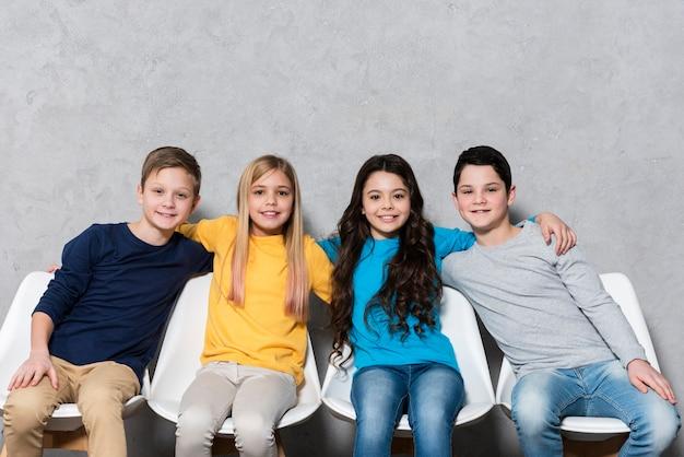 Bambini di angolo basso che si siedono sulle sedie