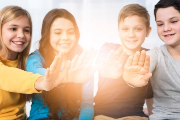Bambini di angolo basso con le mani al sole