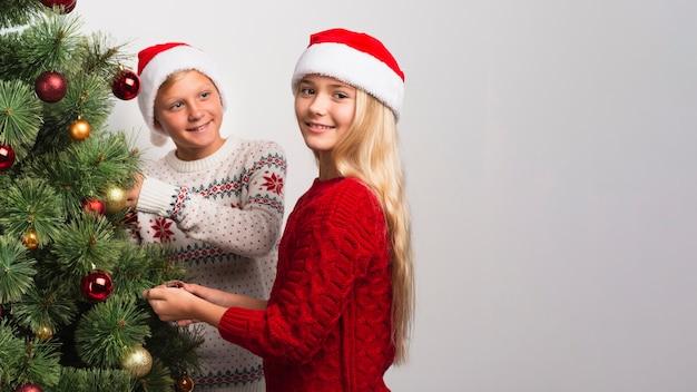 Bambini di natale che decorano l'albero