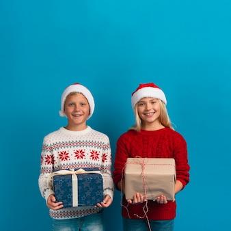 Bambini di natale che tengono il colpo dello studio dei regali