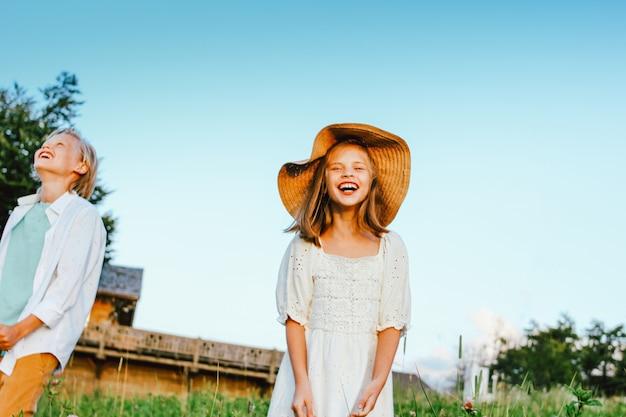 Bambini di risata fratello e sorella amici in erba sullo sfondo del cielo blu, scena rurale