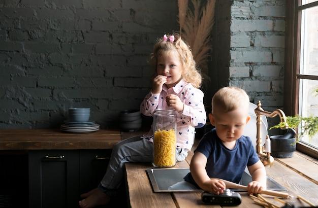 Bambini di tiro medio seduti in cucina