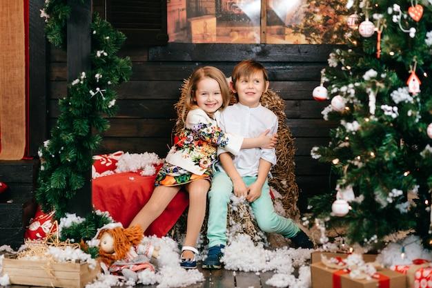 Bambini divertenti che abbracciano nello studio con le decorazioni dell'albero di natale e del nuovo anno.