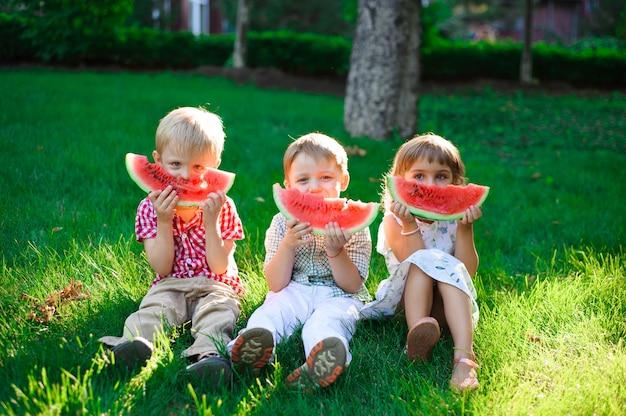 Bambini divertenti che mangiano anguria all'aperto nel parco di estate.