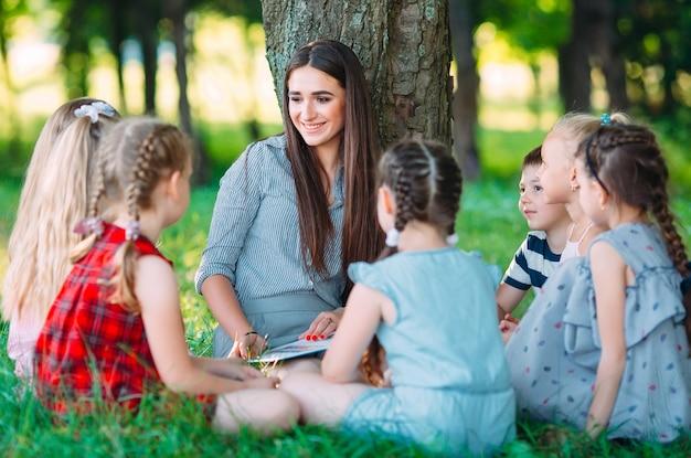 Bambini e istruzione, giovane donna al lavoro come educatore, leggendo un libro per ragazzi e ragazze nel parco