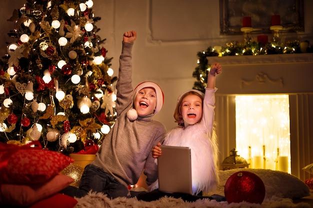 Bambini entusiasti vicino all'albero di natale