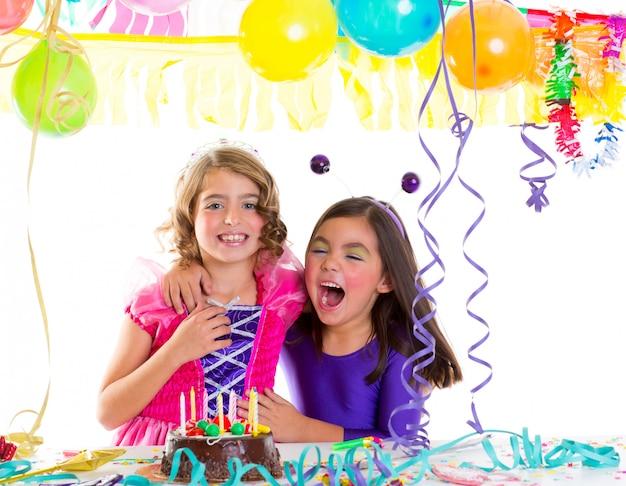 Bambini felici abbraccio in festa di compleanno ridendo