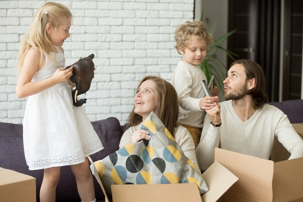 Bambini felici che aiutano i genitori a disimballare le scatole il giorno commovente