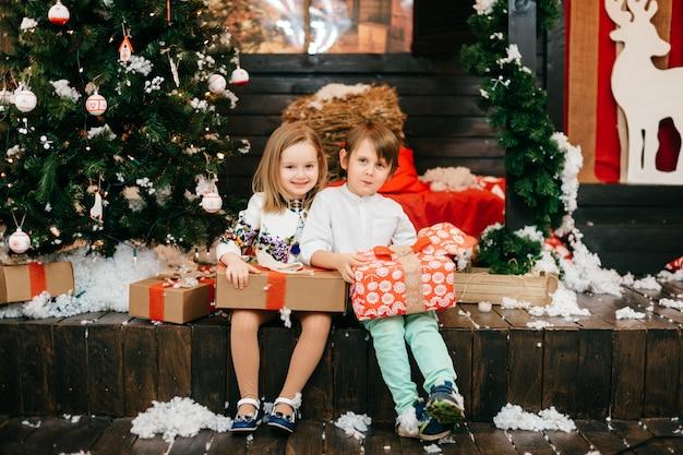 Bambini felici che aprono i contenitori di regalo in studio con l'albero di natale e le decorazioni del nuovo anno.
