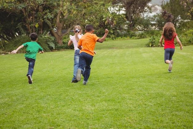 Bambini felici che attraversano l'erba