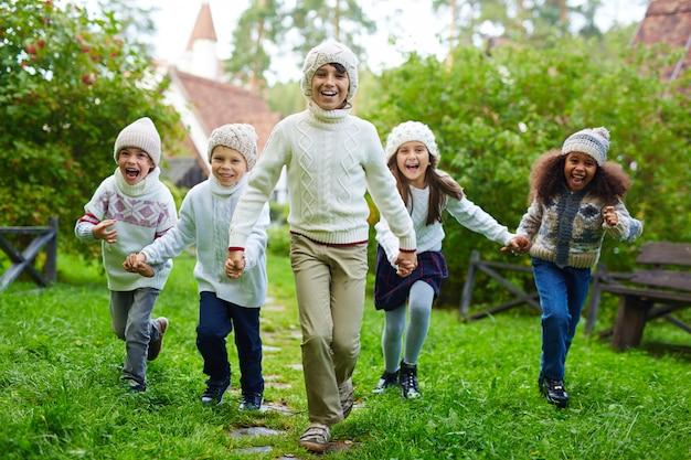 Bambini felici che corrono all'aperto