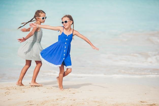Bambini felici che corrono e che saltano alla spiaggia