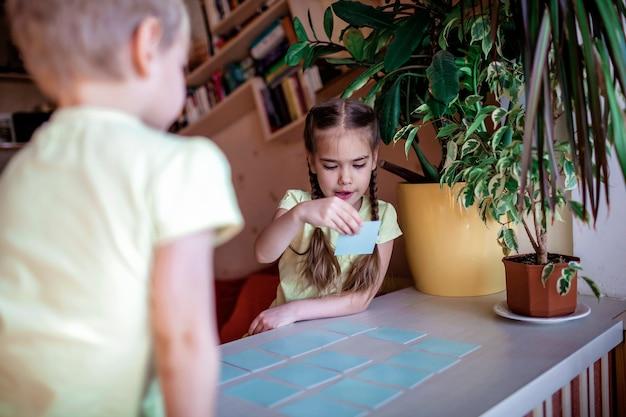 Bambini felici che giocano al memo del gioco da tavolo in interni domestici, valori familiari in realtà