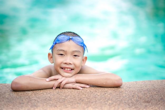 Bambini felici che giocano e che nuotano nella piscina
