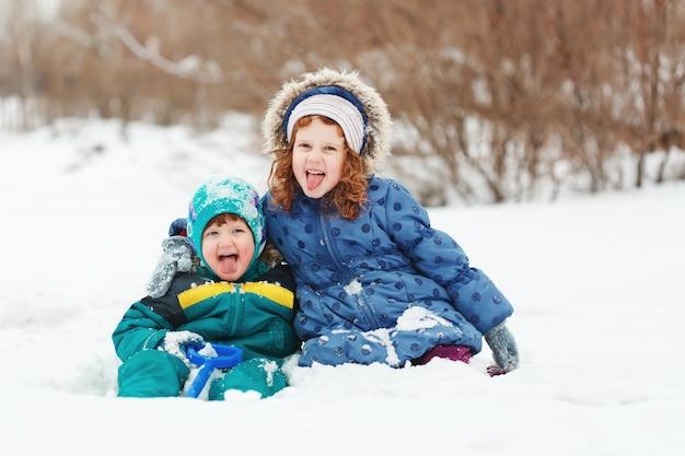 Bambini felici che giocano nel parco invernale.