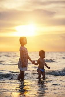 Bambini felici che giocano sulla spiaggia. concetto di felice amichevole sorella e fratello.