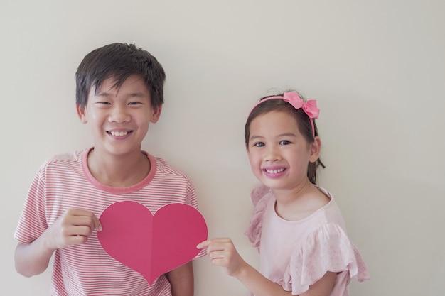 Bambini felici che tengono grande cuore rosso