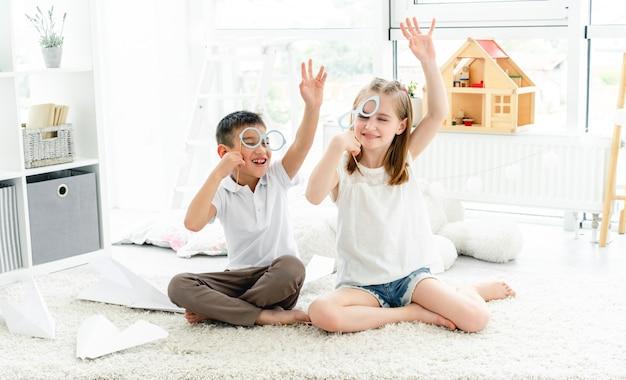 Bambini felici con gli occhiali sui bastoni