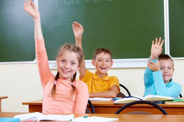 Bambini felici con le braccia fino seduto in aula