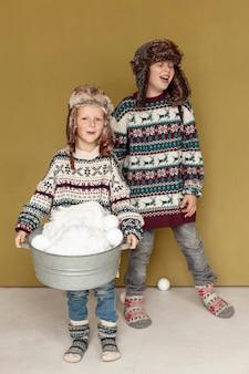 Bambini felici della foto a figura intera che giocano con le palle di neve all'interno