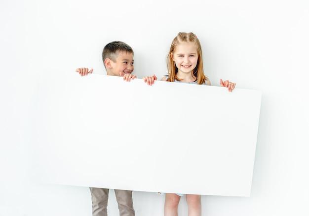 Bambini felici della ragazza e del ragazzo che tengono grande manifesto in bianco