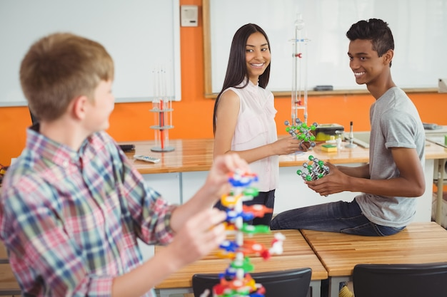 Bambini felici della scuola che sperimentano il modello della molecola in laboratorio
