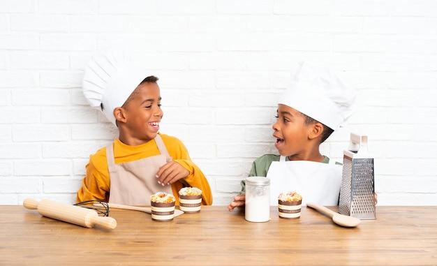 Bambini felici di due fratelli dell'afroamericano vestiti come cuoco unico