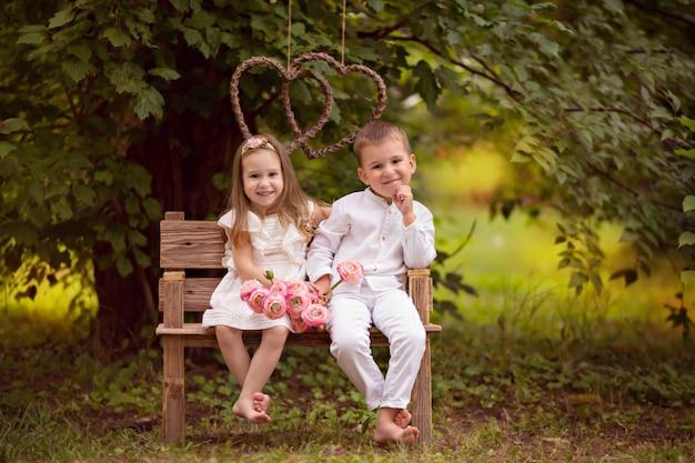 Bambini felici, fratello e sorella, amici nella natura in un parco estivo