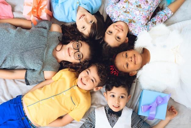 Bambini gioiosi che si trovano sul pavimento a forma di cerchio.