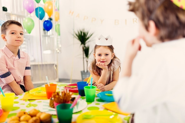 Bambini in berretti colorati seduti al tavolo