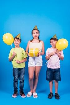 Bambini in cappello di compleanno tenendo regalo giallo e palloncini gialli contro sfondo blu