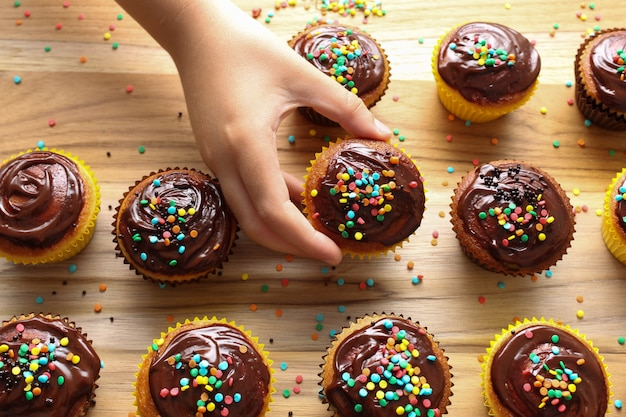 Bambini in cucina! mano del primo piano di un bambino che sceglie un bigné del cioccolato sul bordo del bigné