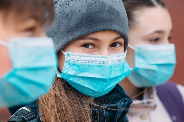 Bambini in età scolare in maschere mediche. ritratto di scolari.