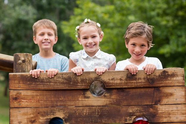 Bambini in piedi su un giro in parco giochi nel parco