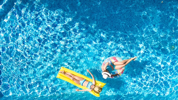 Bambini in piscina vista aerea del drone sopra, bambini felici nuotano su ciambella e materasso ad anello gonfiabili, ragazze attive si divertono in acqua in vacanza con la famiglia in vacanza