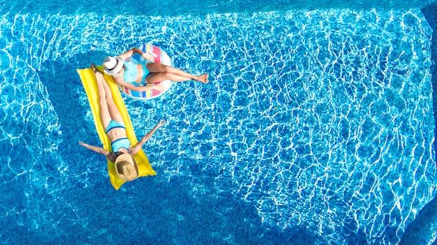 Bambini in piscina vista aerea del drone sopra, bambini felici nuotano sulla ciambella ad anello gonfiabile e materasso, ragazze attive si divertono in acqua in vacanza con la famiglia in vacanza