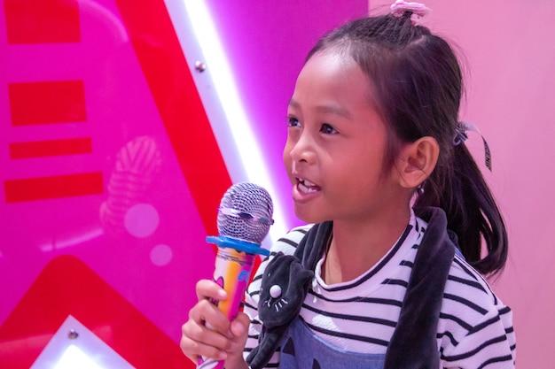 Bambini in possesso di un microfono cantando nella stanza con luci al neon.