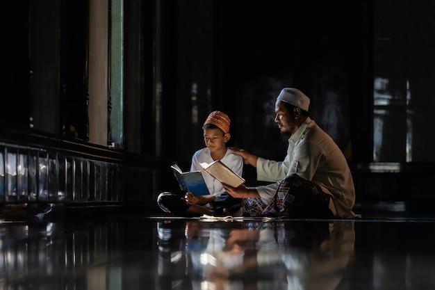 Bambini musulmani ragazzino e insegnante che insegnano indossando camicie bianche facendo il libro di lettura della preghiera