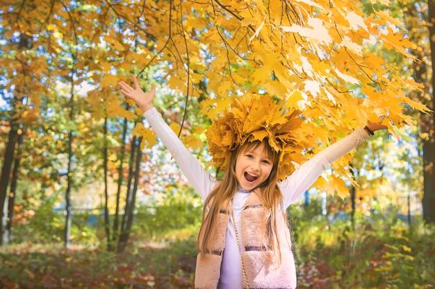 Bambini nel parco con foglie di autunno. messa a fuoco selettiva.