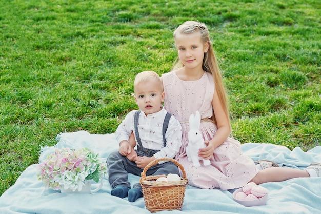 Bambini nel parco il picnic di pasqua con uova e coniglio