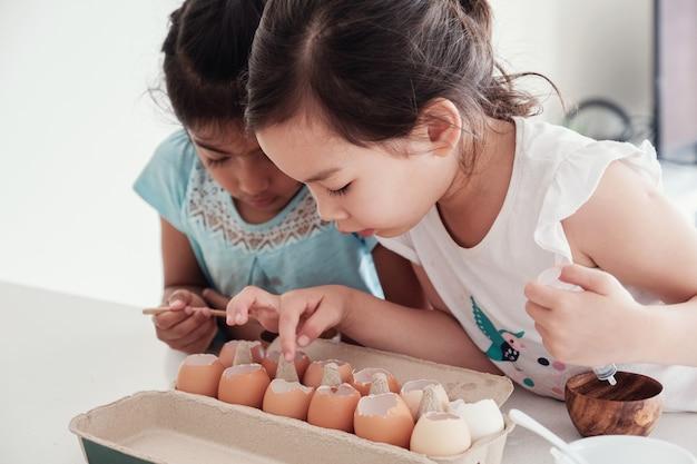 Bambini piccoli che piantano i semenzali nel guscio d'uovo di riutilizzo
