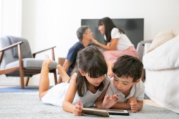 Bambini piccoli concentrati sdraiati sul pavimento in soggiorno e utilizzano dispositivi digitali con app di apprendimento mentre i genitori si baciano