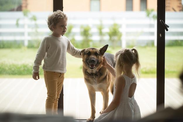 Bambini ragazzo e ragazza che giocano con il cane che entra all'interno della casa