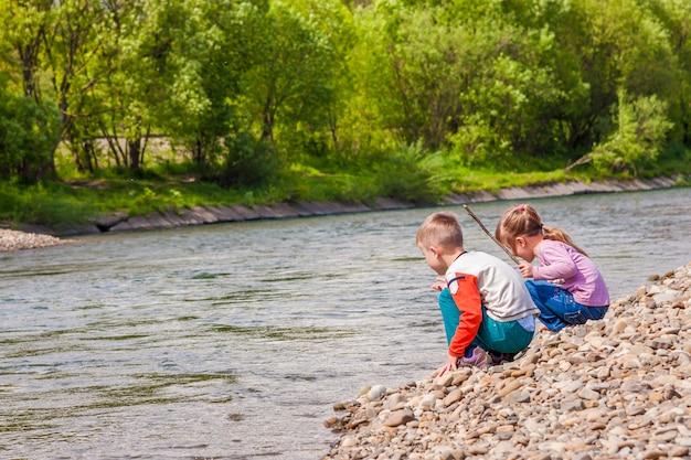 Bambini ragazzo e ragazza che giocano vicino al fiume