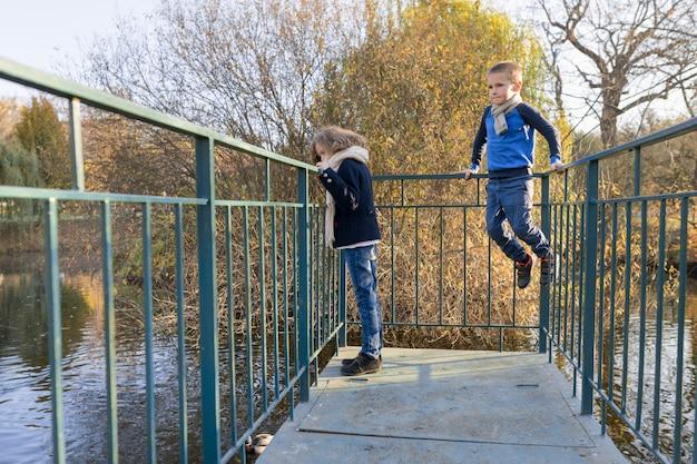 Bambini ragazzo e ragazza in piedi sul ponte, guardando le anatre